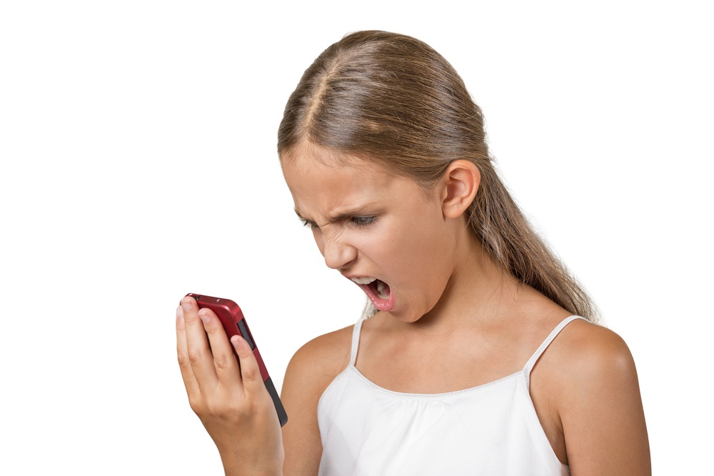 Closeup portrait young mad, frustrated angry teenager girl yelling while on phone isolated white background. Negative human emotion facial expression feelings. Communication, conflict resolution.jpeg