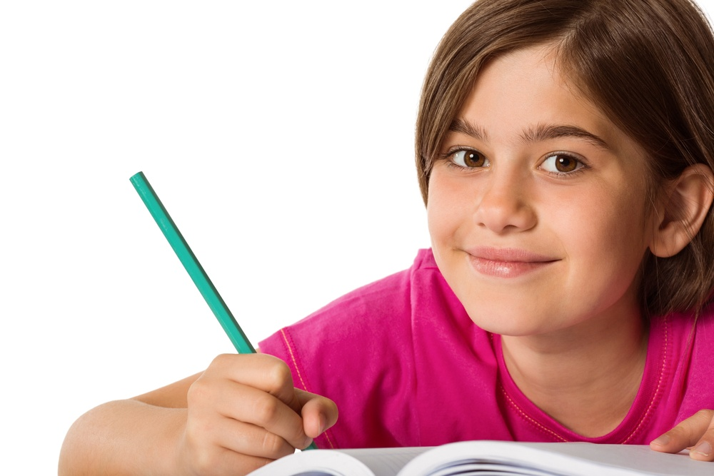 Cute pupil working at her desk on white background.jpeg