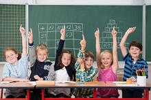 Enthusiastic group of young kids in class sitting in a row at their desk raising their hands in the air to show the know the answer to a question.jpeg