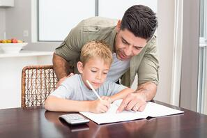 Happy father helping son with math homework at table at home in kitchen-1