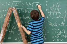 Highly intelligent little boy in the classroom standing on a stepladder to reach a complex mathematical problem on the blackboard that he is busy solving.jpeg