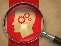 Magnifying Glass with Icon of Profile of Head with Cogwheel Gear Mechanism on Old Paper with Red Vertical Line Background.-1