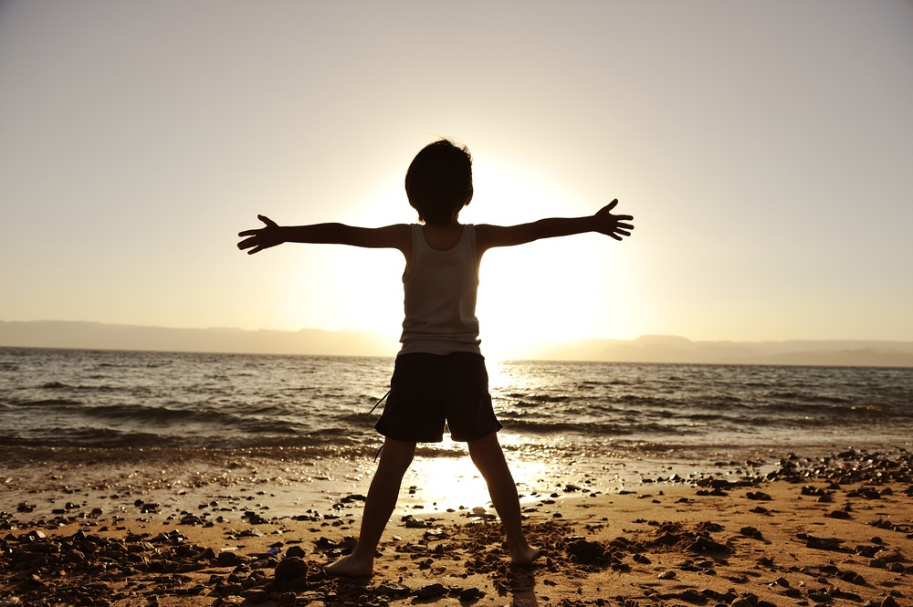 Silhouette of child on the beach, holding his hands up, hugging the sun.jpeg