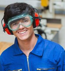 Smiling student standing in a woodwork class and holding a driller-051152-edited.jpeg