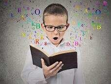 Surprised child reading a book with letters flying away from it isolated on grey wall background. Face expression. Education concept.jpeg