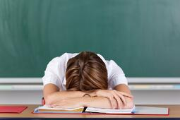 Teacher suffering from acute stress resting her head on her arms at her desk in front of the blackboard as she seeks to gather herself together-1