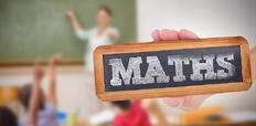 The word maths and hand showing chalkboard against pupils raising their hands during class.jpeg