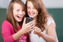 Two laughing students looking at the mobile phone
